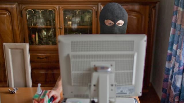Ein Mann, der eine Balaclava trägt, sitzt hinter einem Computerbildschirm