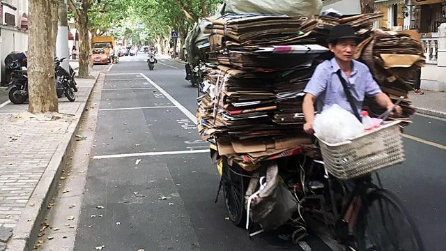 Mann mit Lastenvelo, geladen ein Stapel karton.