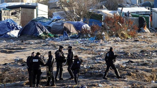 Policists franzos a l'ur dal champ da fugitivs Calais.