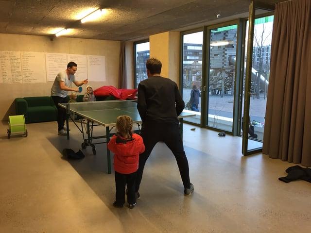 Väter spielen mit Kindern Tischtennis.