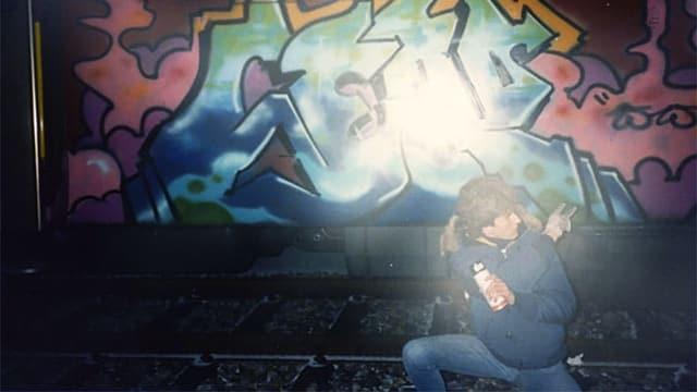Ein Junge steht vor einem mit Graffiti besprayten Zug.