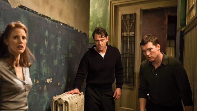 Eine Frau und zwei Männer stehen in einer runtergekommenen Wohnung.