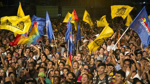 Hunderte Mensschen mit gelben und blauen Flaggen.