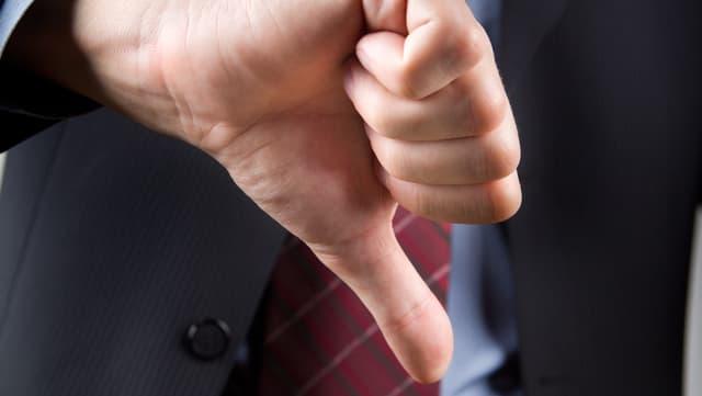 Eine Männerhand formt «Daumen runter». Der Mann trägt einen blauen Anzug und eine rote Kravatte.