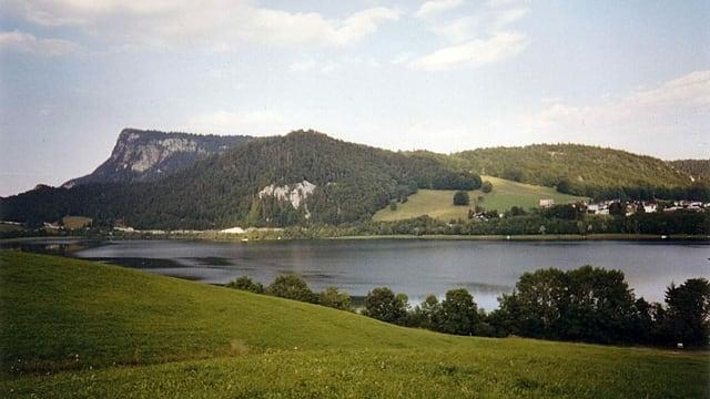 Ein See in grüner hügeliger Landschaft.