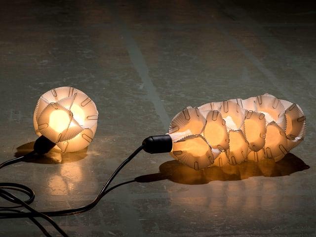 Eine Lampe bestehend aus weissen Muffin-Förmchen, die mit Büroklammern zusammengehalten sind.