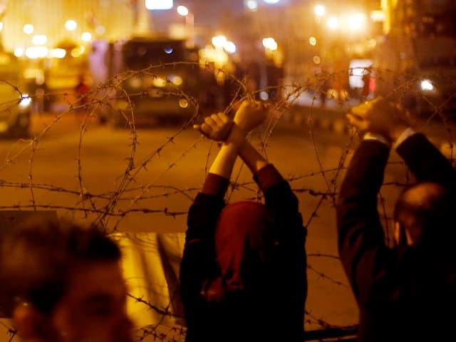 Menschen protestieren hinter Stacheldraht