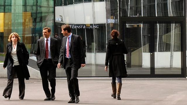 Eine Frau und zwei Männer laufen weg von einem E&Y Gebäude.