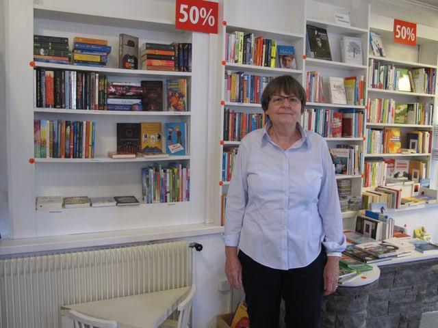 Dorothee Neubauer, kurze Haare, Brille und helle Brille steht vor den Bücherregalen in ihrem Geschäft.