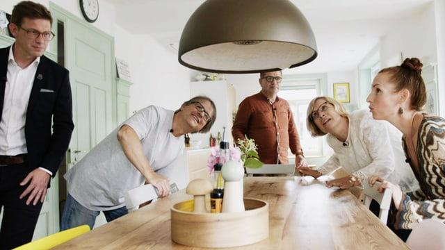 Die fünf Protagonisten der Sendung Wer wohnt wo schauen sich eine Lampe über einem Esstisch an