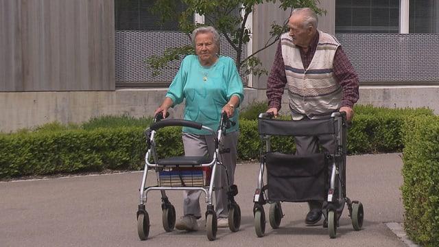 Ein älterer Mann und eine ältere Frau spazieren mit einem Rollator