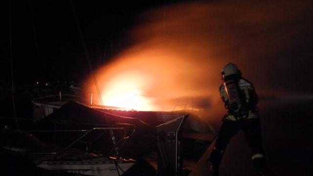 Feuerwehrleute löschen das brennende Segelboot im Bootshafen Aazopf in Arth.