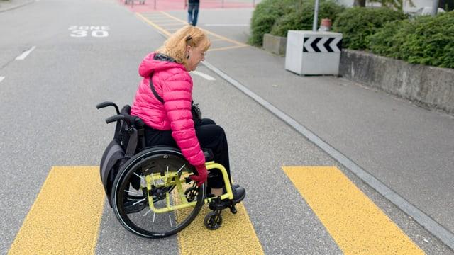 Frau im Rollstuhl überquert Strasse