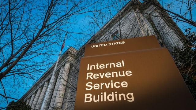 Tafel der Steuerbehörden und Gebäudefassade.