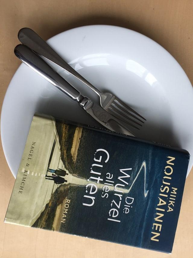 Miika Nousiainen: «Die Wurzel alles Guten» (2017, Nagel + Kimche) auf einem Teller