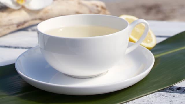 Tasse Tee, hinten eine Zitrone