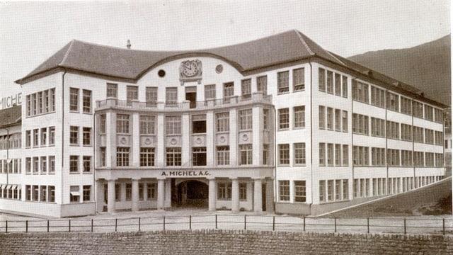 Schwarzweiss-Aufnahme eines Fabrikgebäudes mit Säulen und Uhr.