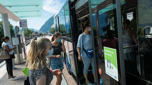 Persunas cun mascras van en in bus public.
