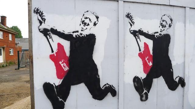 Ein Graffiti-Aufdruck an einer Holzwand in Aldeburgh, der Benjamin Britten mit roter elektrischer Gitarre zeigt.