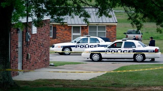 US-Polizeiautos stehen vor einem Gebäude.