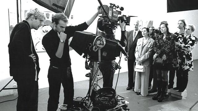 Michael Steiner (links) mit Kameramann Pascal Walder vor einer Gruppe Leute auf einer Schwarz-Weiss-Aufnahme.