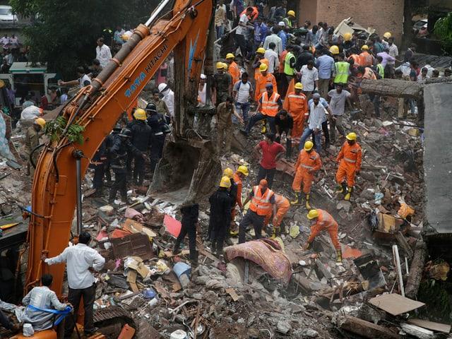 Rettungskräfte suchen in Trümmern nach Überlebenden.