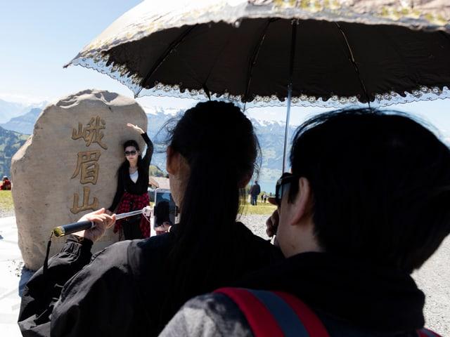Chinesische Touristen machen ein Foto vor einem Stein auf der Rigi.