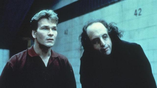 Zwei Männer stehen vor einer Wand und blicken in die gleiche Richtung.