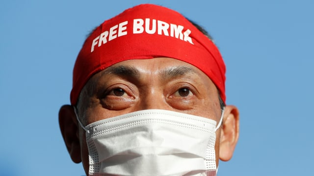 """Ein Demonstrant trägt eine Hygienemaske und auf der Stirn ein Tuch mit der Aufschrift """"Free Burma""""."""
