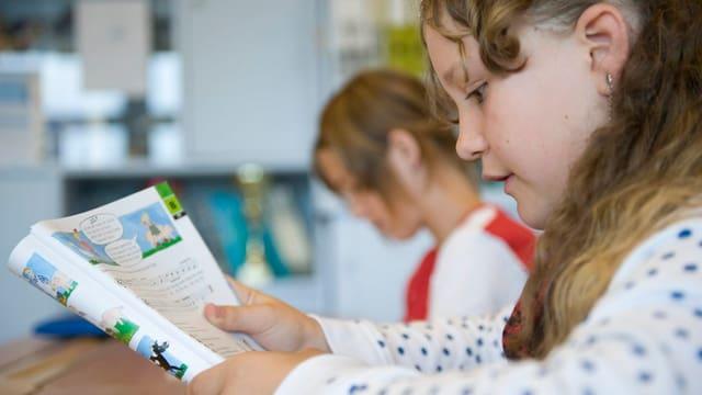 Schulkind, seitlich. das Mädchen hält ein Buch in den Händen und liest.