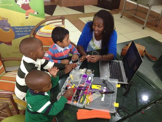 Drei Kinder sitzen um einen Computer herum, eine Frau scheint ihnen etwas zu erklären.