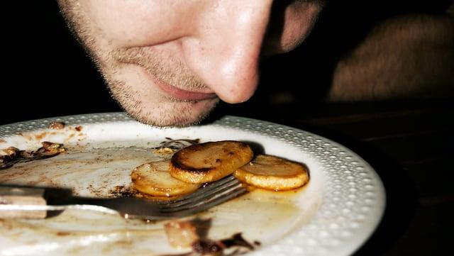 Das Gesicht eines Mannes ganz nah an einem Teller.