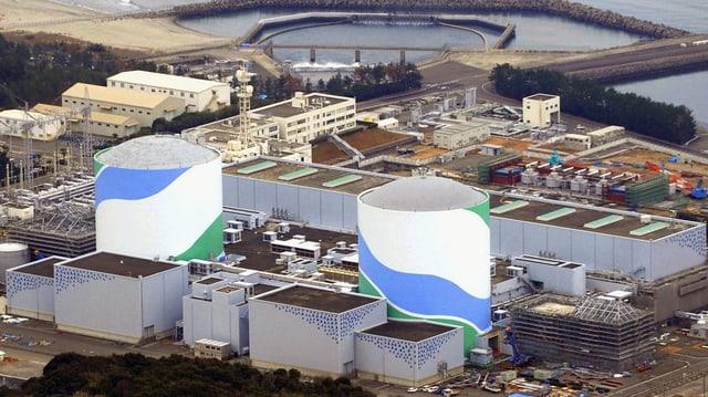 Dus reacturs da l'ovra atomara cun containers, sper la mar.