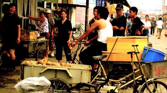 Strassenszene, Mann auf Fahrrad an Lebensmittelgeschäft, einige Frauen um ihn herum