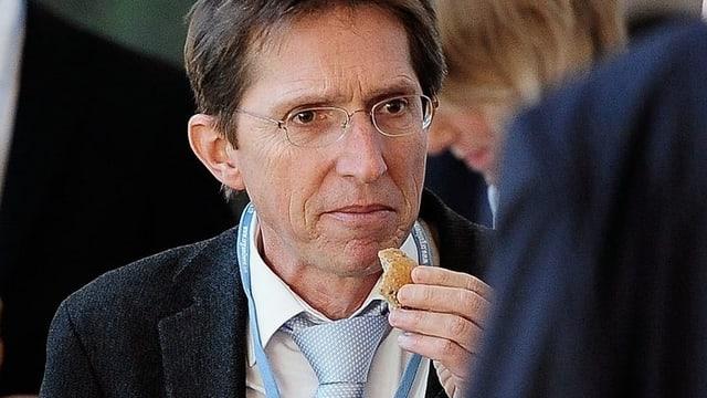 Michael Jordi, mit hellblauer Krawatte, beisst bei einem Apéro in ein Brötchen.