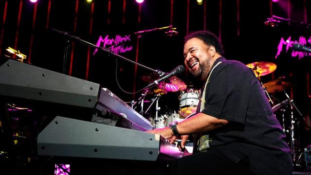 Ein schwarzer Musiker spielt Keyboard und singt.