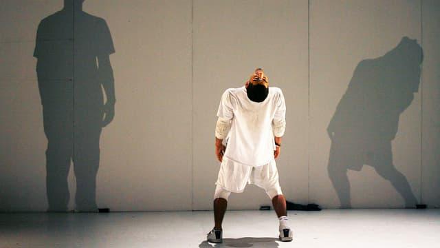 Ein Mann steht auf der Bühne, mit dem Rücken zum Publikum.