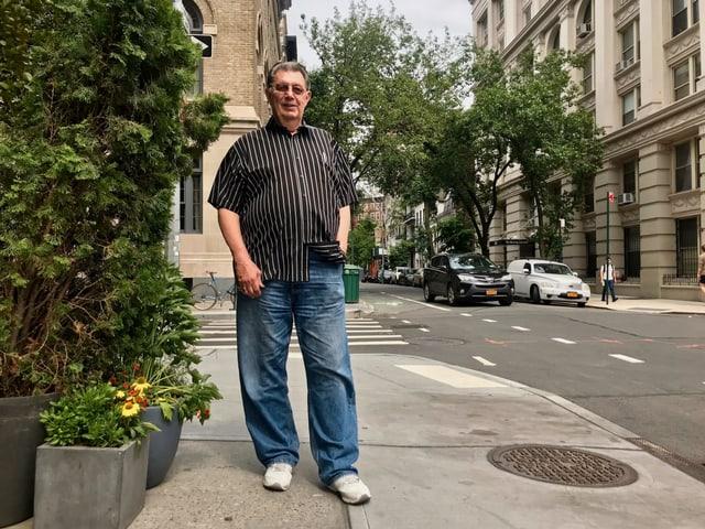 Ein Mann steht auf dem Troittoir in einer Grosstadt. Hinter ihm eine leere Strassenkreuzung mit Fussgängerstreifen.