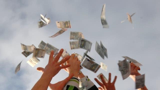 Hände fangen in die Luft geworfene Geldscheine. (Symbolbild)