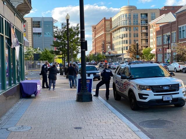 Die Polizei steht gegenüber einer Apotheke und treibt sich versammelnde Gruppen auseinander.