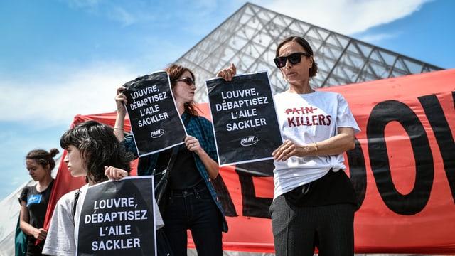 Leute protestieren vor dem Pariser Louvre. Sie halten Transparente in der Hand.