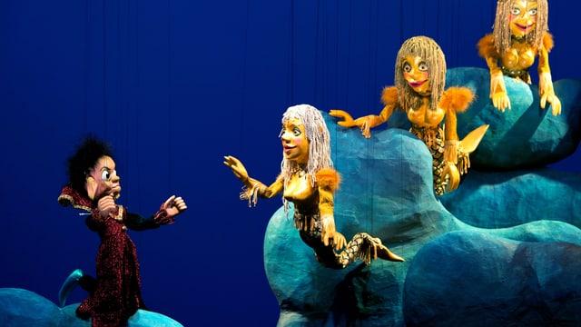 Vier Marionetten, drei Meerjungfrauen und ein Kasperl in rotem Gewand.