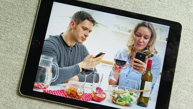 Ein Mann und eine Frau beim Essen starren in ihre Handys.