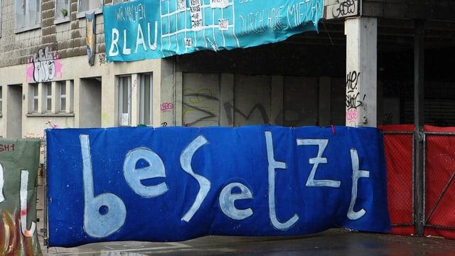 """Vor einer Hausfassade hängt ein Banner mit der Aufschrift """"besetzt""""."""