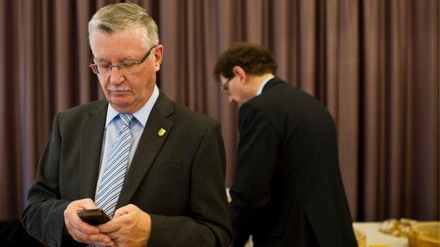 Finanzdirektor Bernhard Koch schaut auf sein Natel. Im Hintergrund ist Jakob Stark zu sehen.