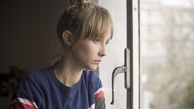 Eine junge Frau schaut traurig aus dem Fenster.