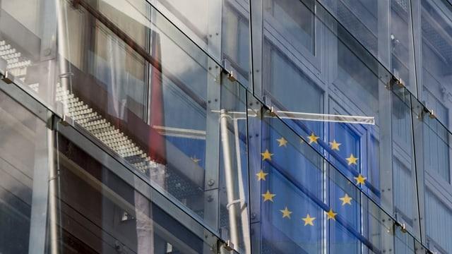 Bandieras da Svizra ed EU che reflecteschan en il vaider d'in bajetg.