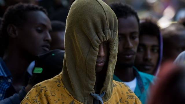 Mann mit Kapuze, Schwarzafrikaner, wartet