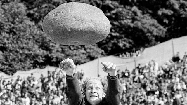 Ein Mann wirft einen grossen Stein.