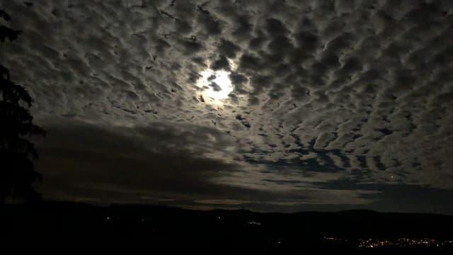 Das Licht des Vollmondes dringt durch die Wolkenschicht.